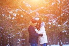 Étreintes heureuses de jeune homme et de femme dans la forêt d'hiver Photo stock