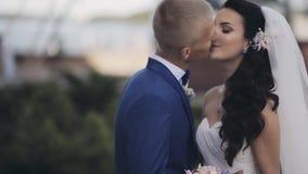 Étreintes heureuses de nouveaux mariés dehors en nature Beau marié et jeune mariée embrassant, passant tendrement le temps ensemb banque de vidéos