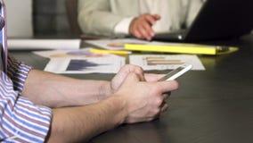 Étroit cultivé d'un homme d'affaires dactylographiant à son téléphone intelligent au bureau banque de vidéos