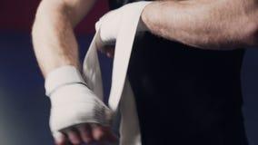 Étroitement, boxeur enveloppant des mains avec les bandages élastiques avant combat, mouvement lent banque de vidéos