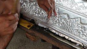 Étroitement des mains de l'artisan travaillant au panneau argenté banque de vidéos