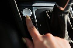 Étroitement du doigt de la femme appuyant sur le bouton de début et de fin de moteur sur la voiture images libres de droits