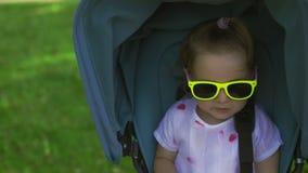 Étroitement : Fille mignonne regardant et souriant la caméra se reposant dans la voiture d'enfant bleue - scène chaude d'été de c clips vidéos