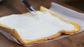 Étroitement, mains de crème de propagation de confiseur méconnaissable sur le gâteau mousseline en faisant la bûche à la maison banque de vidéos