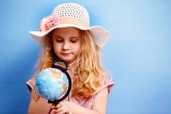 Étude blonde de fille d'enfant le globe Concept de voyage et d'aventure Images libres de droits