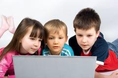 Étude d'enfants avec un ordinateur portatif Photo stock
