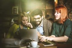 Étude sur l'ordinateur portable Amis au café Image stock