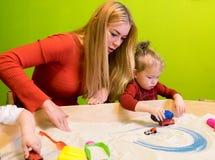Études se développantes de personnes européennes blanches de mère et de fille du développement précoce avec le sable dans le bac  Photos libres de droits