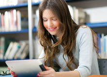Étudiant à l'aide d'un comprimé dans une bibliothèque Images libres de droits