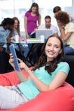 Étudiant à l'aide du comprimé numérique avec des amis à l'arrière-plan Photos stock