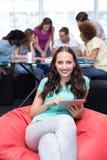 Étudiant à l'aide du comprimé numérique avec des amis à l'arrière-plan Image stock