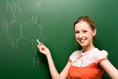 Étudiant écrivant des symboles chimiques Photographie stock libre de droits