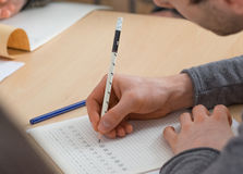 Étudiant écrivant les caractères chinois Photographie stock