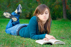 Étudiant affichant un livre en stationnement Photographie stock