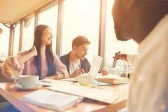 Étudiant afro-américain agréable s'asseyant à la table avec des groupmates Images stock