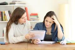 Étudiant aidant son ami frustrant à apprendre la leçon Image stock