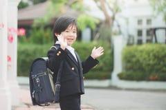 Étudiant allant à l'école et ondulant au revoir Photographie stock