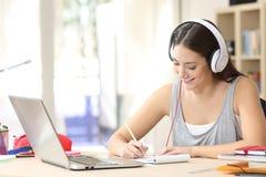 Étudiant apprenant avec des écouteurs prenant des notes images stock
