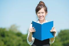 Étudiant asiatique en parc avec le livre et la note de conférence Photo libre de droits