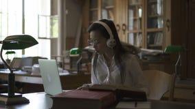Étudiant asiatique féminin en verres ronds écoutant la musique banque de vidéos