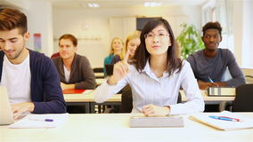 Asian student raising hand in classroom Stock Footage
