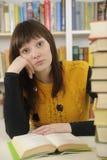 Étudiant avec des livres dans une bibliothèque Photos libres de droits