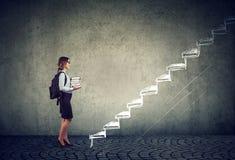 Étudiant avec des livres se tenant sur les escaliers de l'éducation menant au succès images stock