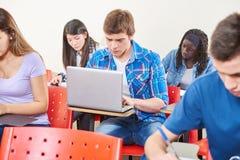 Étudiant avec l'ordinateur portable à l'école photographie stock