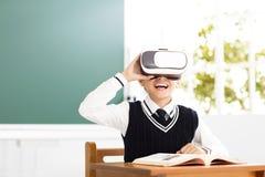 Étudiant avec le casque de réalité virtuelle se reposant dans la salle de classe photos libres de droits