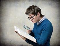 Étudiant avec le livre et la loupe Photos stock