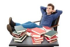 Étudiant ayant un repos avec les jambes sur le bureau, AMO de rêverie Photo libre de droits