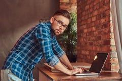 Étudiant bel dans une chemise de flanelle travaillant sur un ordinateur portable dans une chambre avec un intérieur de grenier Photos stock