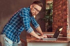 Étudiant bel dans une chemise de flanelle travaillant sur un ordinateur portable dans une chambre avec un intérieur de grenier Photo libre de droits