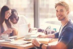 Étudiant bel positif s'asseyant à la table avec ses amis Photos stock