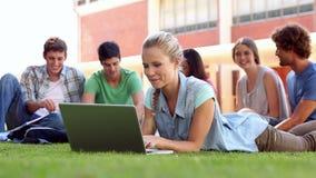 Étudiant blond à l'aide de l'ordinateur portable avec des camarades de classe s'asseyant derrière sur l'herbe banque de vidéos