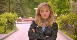 Étudiant blond caucasien frais posant dans la caméra étant sûre avec les mains croisées en parc vert de ville clips vidéos