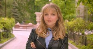 Étudiant blond caucasien joyeux posant dans la caméra étant sûre avec les mains croisées en parc vert de ville banque de vidéos