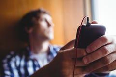 Étudiant bouleversé regardant par la fenêtre et la musique de écoute Images libres de droits