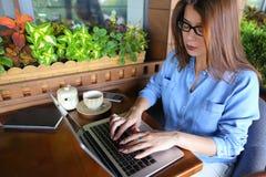 Étudiant causant par l'ordinateur portable avec des amis au café Photographie stock