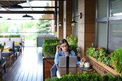 Étudiant causant par l'ordinateur portable avec des amis au café Image libre de droits