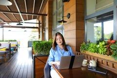 Étudiant causant par l'ordinateur portable avec des amis au café Images libres de droits