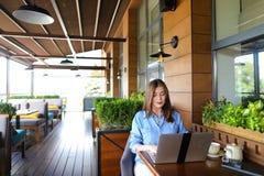 Étudiant causant par l'ordinateur portable avec des amis au café Photographie stock libre de droits