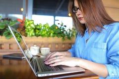 Étudiant causant par l'ordinateur portable avec des amis au café Photo stock