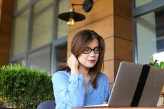 Étudiant causant par l'ordinateur portable avec des amis au café Photo libre de droits