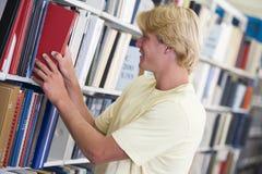 Étudiant choisissant le livre à partir de la bibliothèque Photos stock