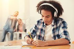 Étudiant concentré écoutant la musique et faisant des notes Photo stock