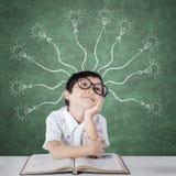 Étudiant d'école primaire avec l'ampoule branchue photos stock