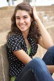Étudiant d'adolescent de sourire s'asseyant à l'extérieur Photographie stock libre de droits