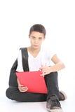 Étudiant d'adolescent sérieux s'asseyant sur l'étage Photographie stock libre de droits