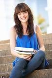 Étudiant d'adolescent s'asseyant à l'extérieur sur des opérations d'université Image stock